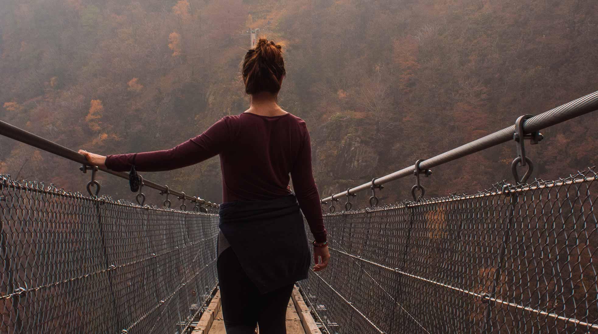 En kvinna går över en hängbro. Foto: Susanna Marsiglia / Unsplash