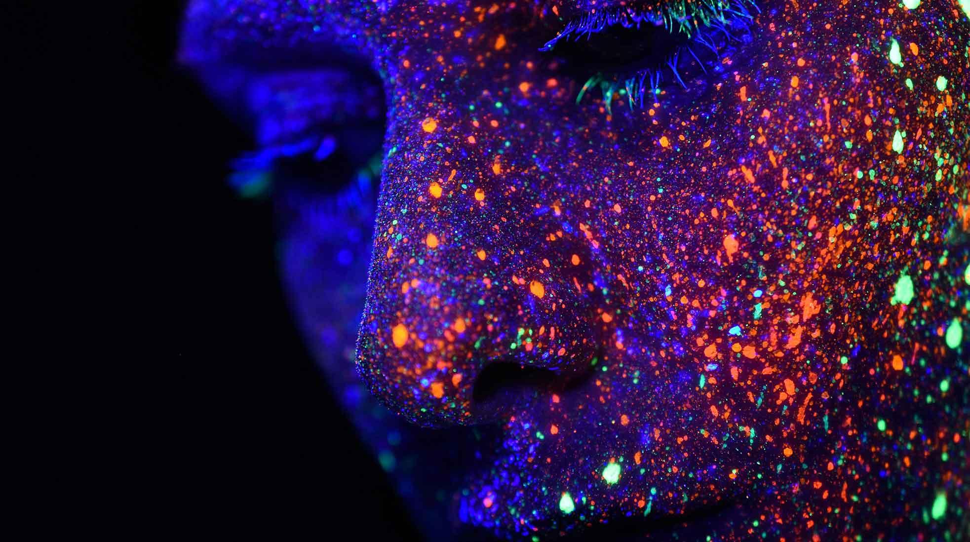En suggestiv bild av ett mänskligt ansikte täckt med färgade prickar