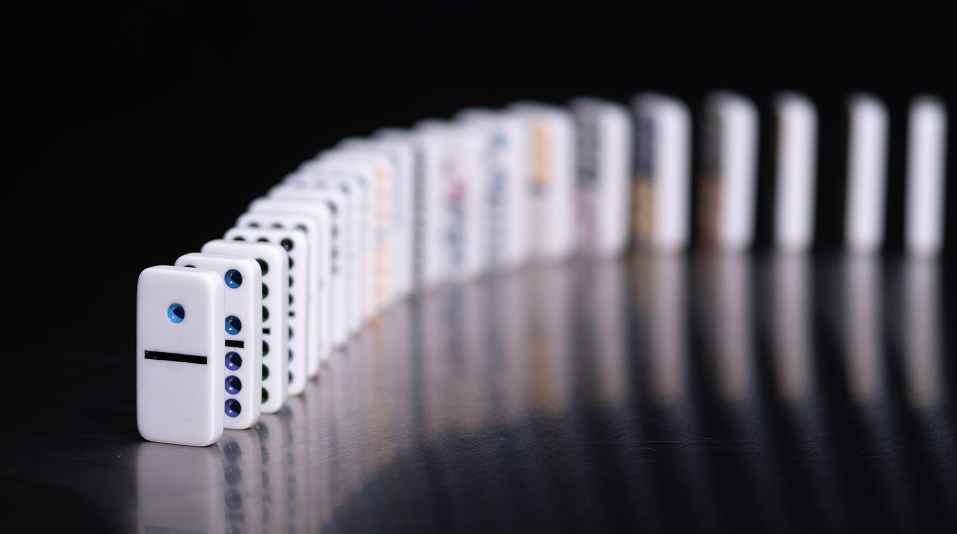 Vita dominobrickor står uppställda i en kedja på ett svart underlag