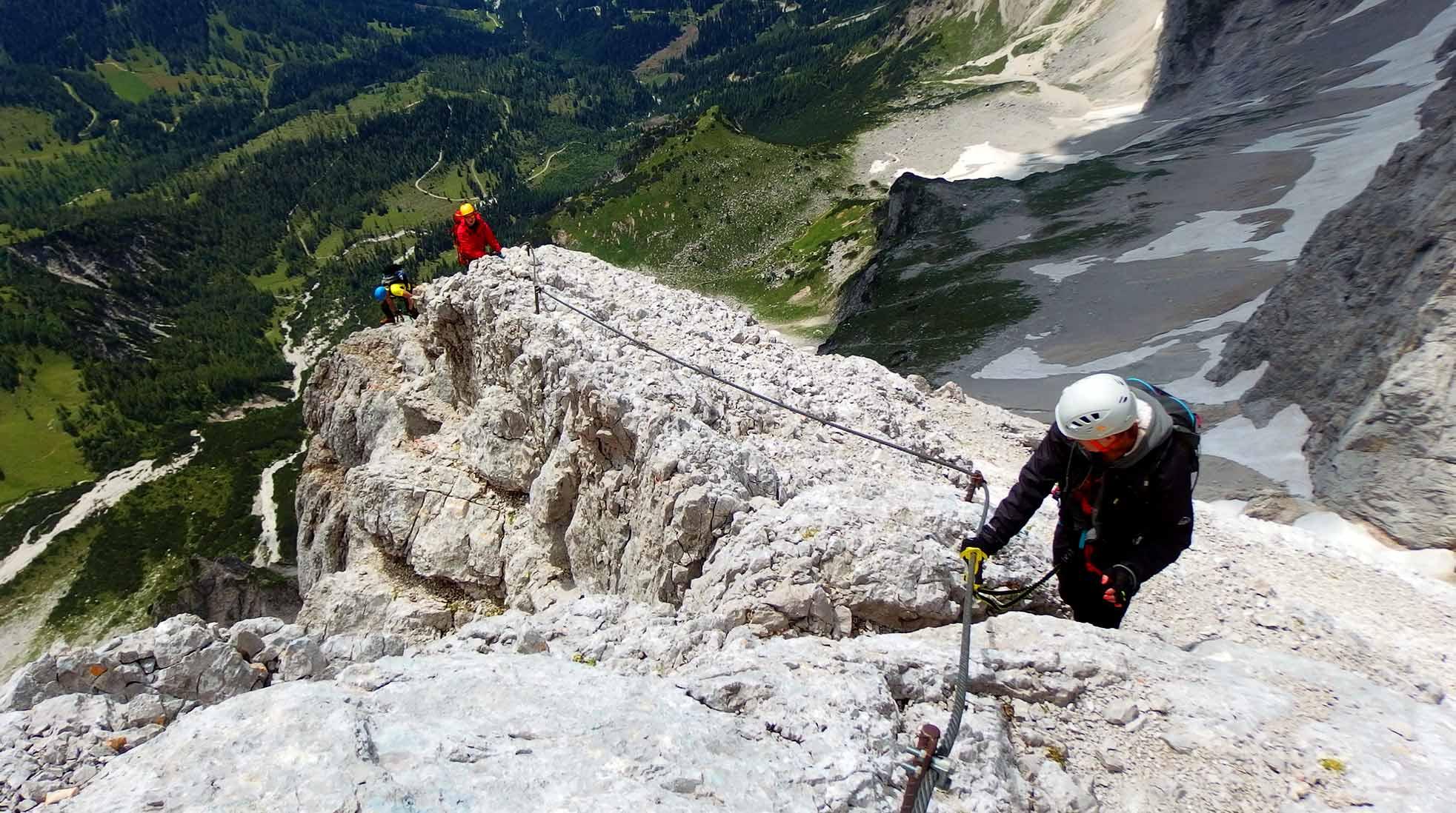 Tre människor klättrar upp för en Via Ferrata på en bergssluttning i alperna