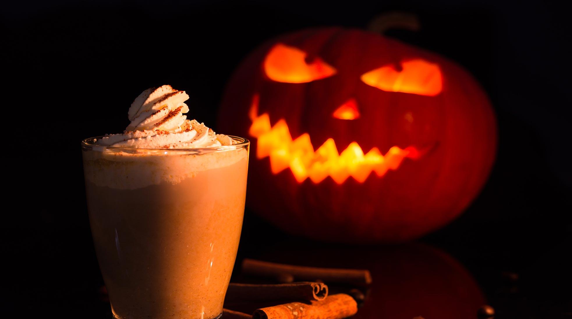 En caffe latte toppad med vispad grädde framför en orange halloweenpumpa